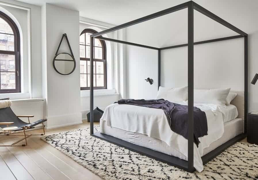 A modish Scandinavian-Style primary bedroom with a stylish bed set and a handsome rug covering the hardwood flooring.