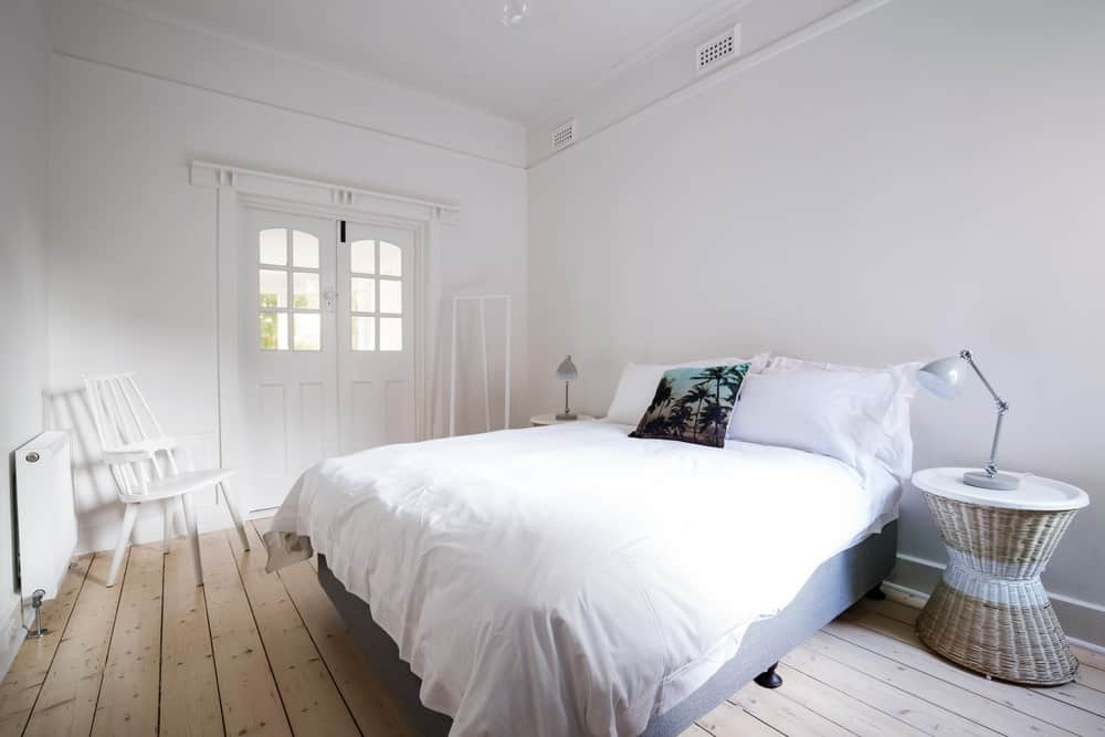 White Scandinavian-Style primary bedroom featuring a white chair on the corner and two stylish side tables set on the hardwood flooring.