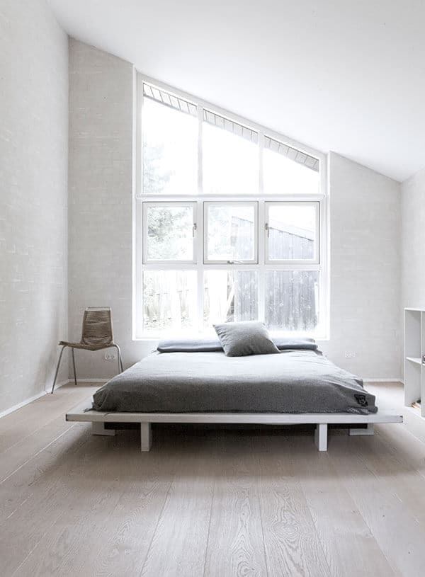 The white shed ceiling of this Scandinavian-Style bedroom is complemented by a tall window that follows the shape of the ceiling. It is at the head of the bed cushion that is on a charming white wooden platform that matches the white floor and walls.