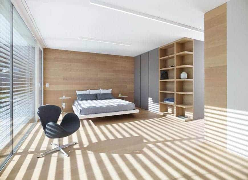 This Scandinavian-Style primary bedroom has a bed on a floating platform that is attached to a wooden wall flanked by two modern bedside tables. It has glass walls on one side and on the other is a huge wooden structure that has built-in cabinets and shelves.