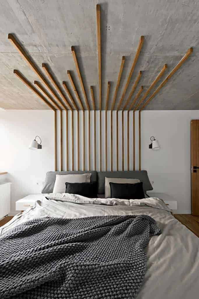The wooden bed of this Scandinavian-Style bedroom has a peculiar headboard that also acts as wall and ceiling decoration. It has wooden striped slats running from the headboard up the wall and to the middle of the ceiling. This is flanked by two wall-mounted white lamps over white bedside tables.