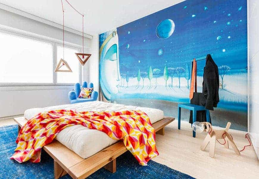 This Scandinavian-style bedroom appeals to your inner peace and inner child with its vibrant colors and shapes paired with Buddhist imagery. This is complemented by a simple white bed cushion on a wooden platform for its bed that adds to its simplicity.