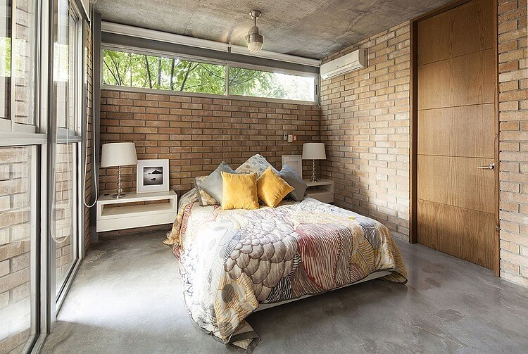 The gray concrete flooring of this industrial-style bedroom matches with the gray concrete ceiling that supports a semi-flush mounted light over the bed with a colorful sheet that complements the red brick walls.