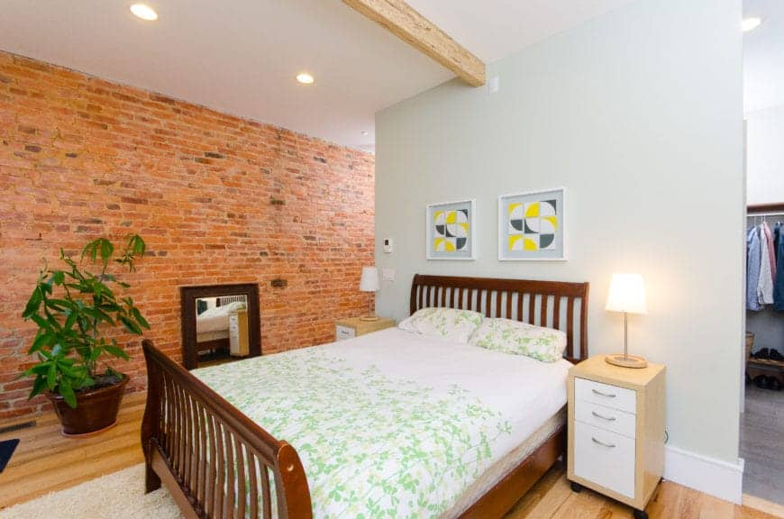 The wooden sleigh bed has a wooden headboard with a slat finish that stands out against the light gray wall topped with a white ceiling with a single wooden beam in the middle. This pairs well with the red brick wall and hardwood flooring.