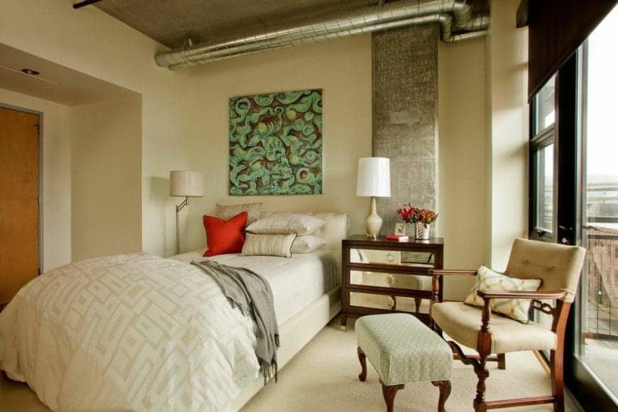 This charming primary bedroom is a lovely fusion of traditional-style and industrial-style. It has a traditional bed that complements the beige carpeted flooring and beige walls. This is accented with exposed pipes and vents of the concrete ceiling.