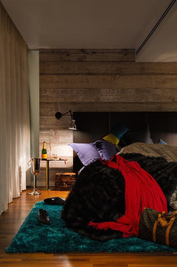The black cushioned headboard of the traditional bed is against a wall made of distressed wooden planks that stand out against the white ceiling and the redwood flooring. This wall supports a wall-mounted lamp over the stainless steel bedside table.