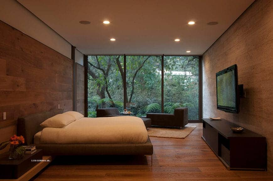 The white ceiling has recessed lights that cast down warm yellow lights onto the hardwood flooring that extends to the walls at the head and foot of the brown bed. This is given a nice background of lush greenery outside the glass wall.