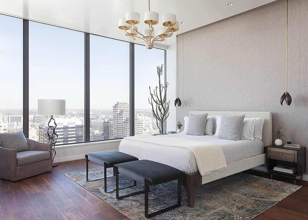 The dark hardwood flooring of this primary bedroom is brightened by the large glass walls on the right side of the bed that has a light gray headboard against a gray concrete wall accented with a pair of flower-like pendant lights.