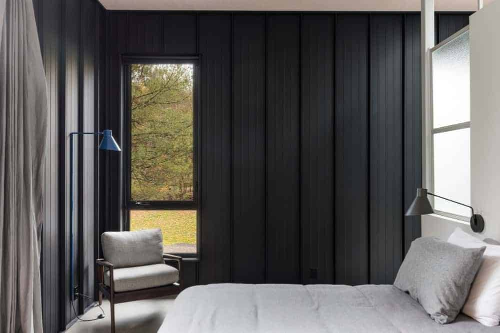 The light gray sheets of the bed matches with the gray concrete flooring and the cushions of the wooden armchair by the window that is inlaid into the industrial-style walls of dark gray material.