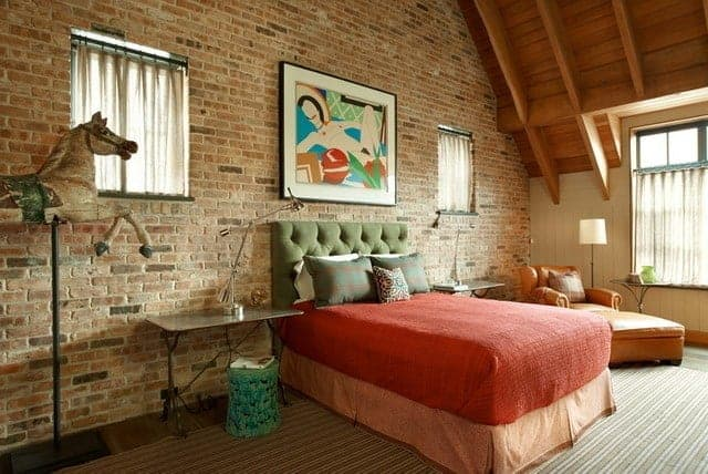 The green tufted headboard of the traditional bed is against a textured red brick wall adorned with a colorful painting flanked with square curtained windows. Beside the bed is a brown leather single sofa chair that matches with the wooden ceiling that has exposed wooden beams.