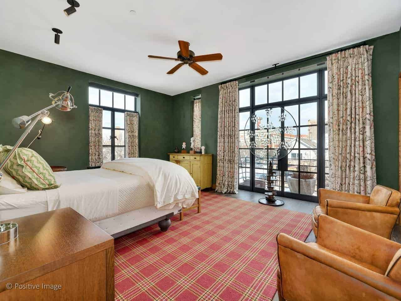 This industrial-style primary bedroom has dark green walls that are contrasted by the large French window and French glass doors. These are paired with floral curtains that pairs with the red plaid area rug to bring a dash of color to the bedroom.
