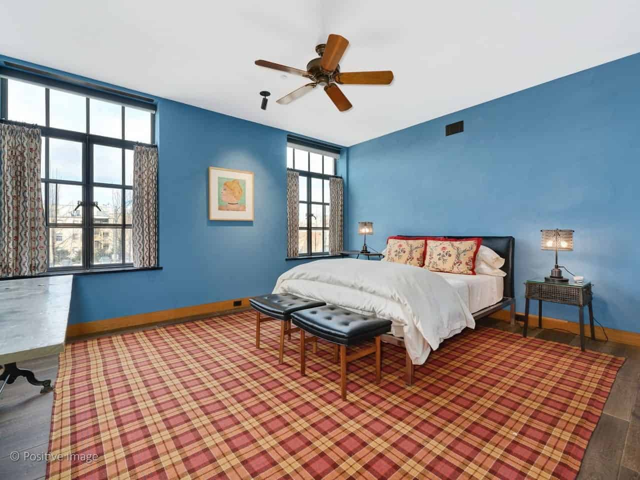 The hardwood flooring is covered with a red area rug that has a plaid pattern to it that provides a nice complex and colorful background for the black leather bed with stainless steel legs flanked with a couple of industrial-style bedside tables with matching table lamps.