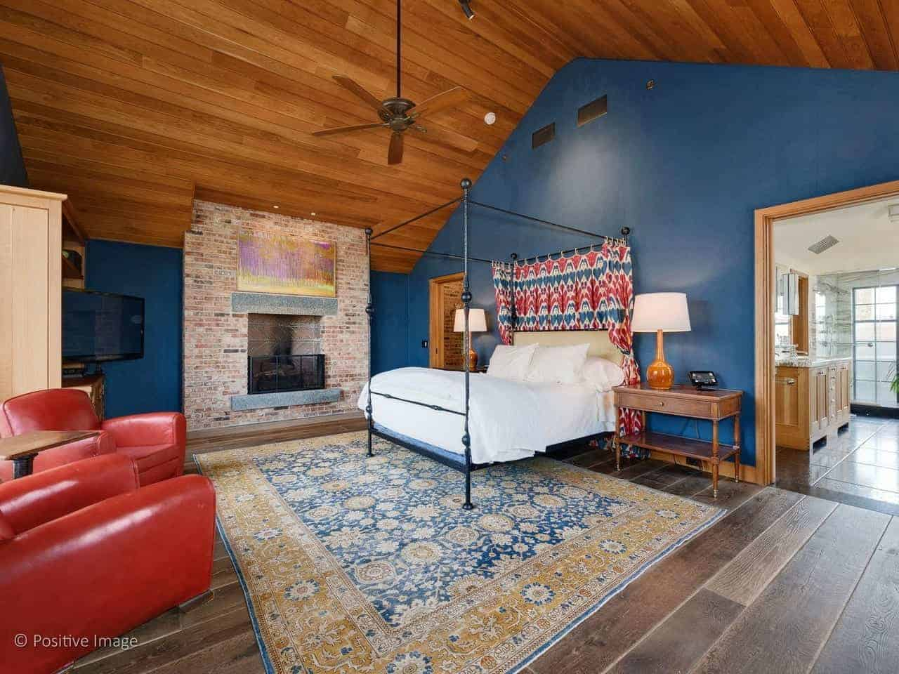 This industrial-style primary bedroom has the warm embrace of a traditional fireplace that is inlaid with red bricks. This stands out against the blue walls but complements the wooden cathedral ceiling that has a ceiling fan over the four-poster bed.