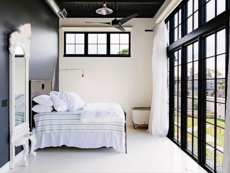 The brightness of this bedroom is due to the natural lights coming in from the French glass doors that brighten the white flooring and wall adjacent to the black headboard of the traditional bed topped with a ceiling with exposed beams, vents and tubes.