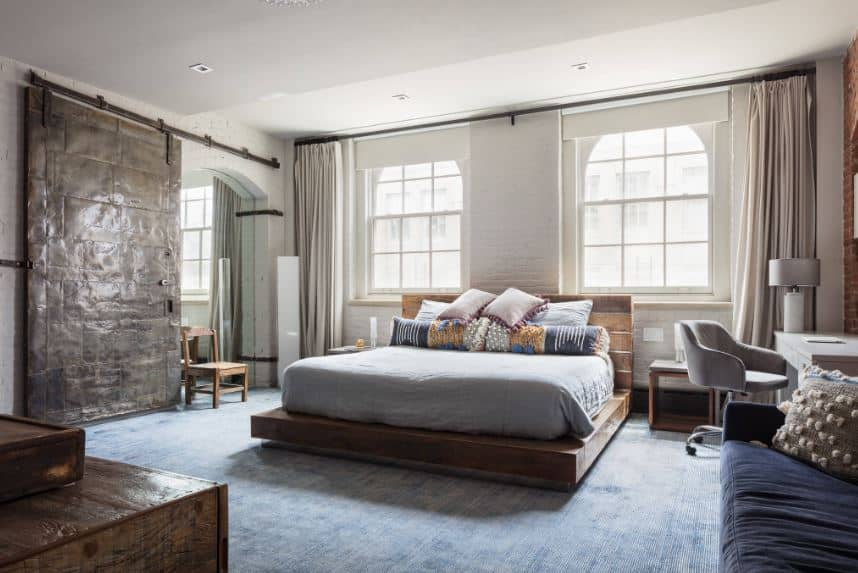 The blue distressed carpeting of the floor is a nice complement to the wooden platform with a plank finish to its wooden headboard that stands out against the white walls brightened by the natural lights of the arched windows.