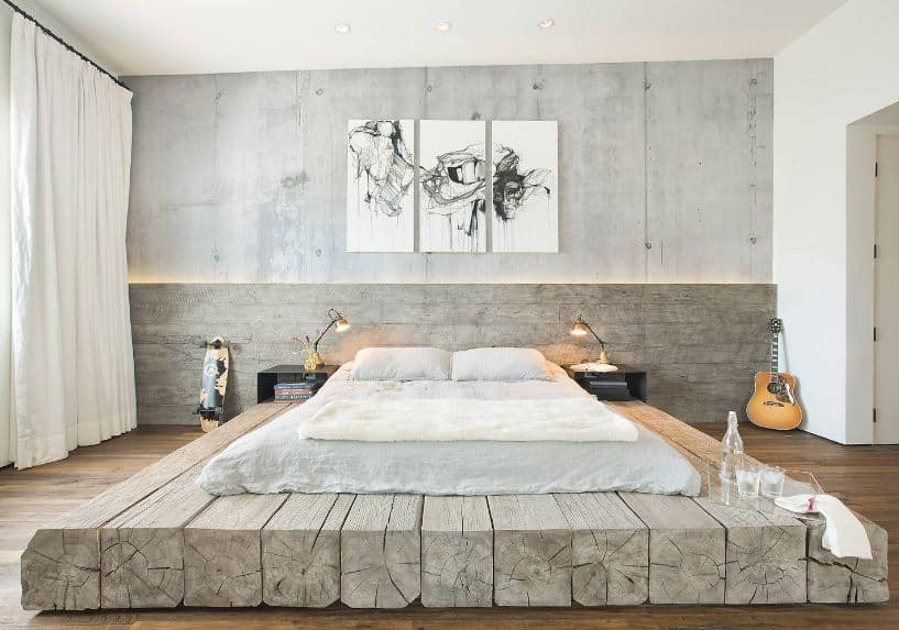 The white cushion is placed on a large platform made of several wooden beams beside each other. This complements the hardwood flooring that matches with the gray concrete wall adorned with framed artworks.