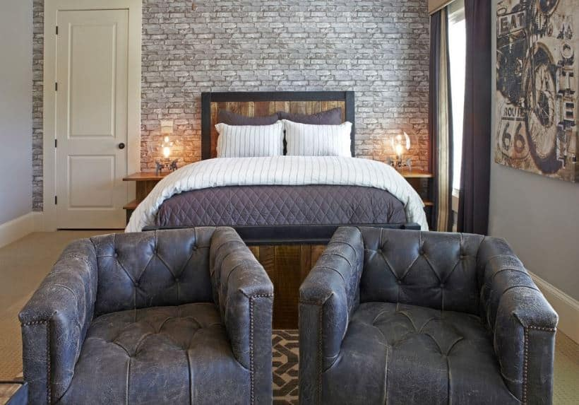 The couple of worn out gray tufted armchairs at the foot of the bed goes well with the industrial-style aesthetic of the bedroom that has gray brick walls behind the wooden headboard of the bed that looks like it came from a barrel.