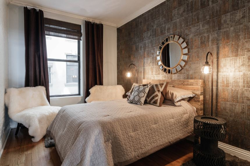 The wall behind the wooden headboard of the traditional bed has a wallpaper with a design that is distinctly industrial-style. This is augmented by a couple of industrial-style lamps peculiar industrial-style bedside tables.