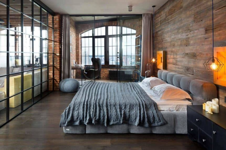 This industrial-style primary bedroom is separated from the rest of the house with glass walls that go well with the dark hardwood flooring. On the far wall is a small office with a large arched window and red brick walls that match the wooden wall of the gray cushioned headboard.