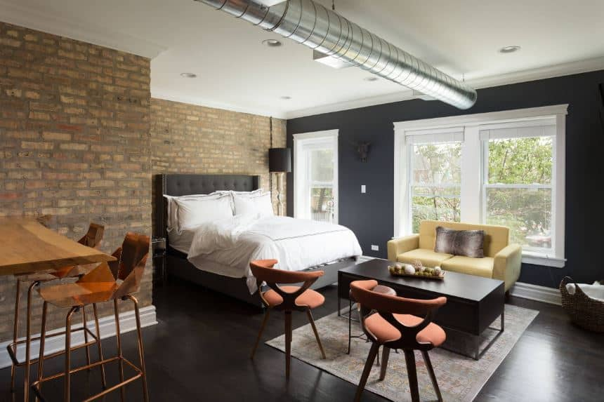 The black hardwood flooring is matched with the black wall that supports the white framed windows topped with a stainless steel exposed vent of the white ceiling contrasted by brick walls near the dark gray cushioned bed.
