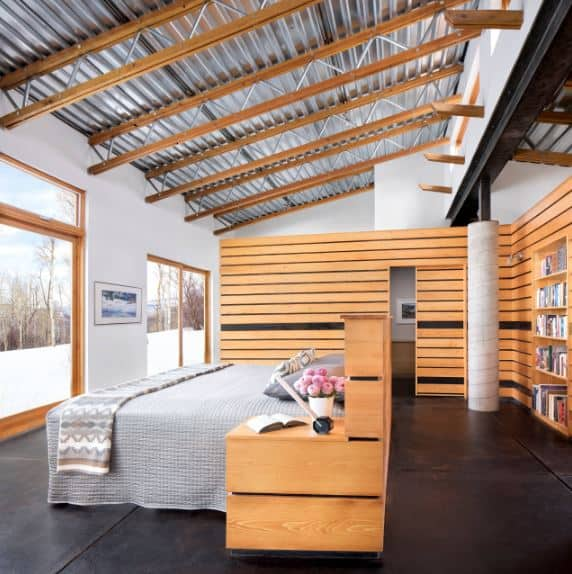 The gray bed sits in the middle of the black industrial flooring contrasted by the light wood headboard and bedside drawer of the bed as well as the walls surrounding the bed. This is topped with a factory-like ceiling of metal beams and tin roofing.