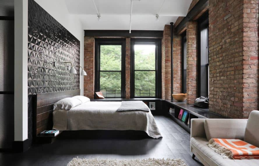 This industrial-style primary bedroom is surrounded with tall windows that are supported by brick pillars framed with black wooden shelves at the bottom that matches with the black wall panel behind the wooden headboard.