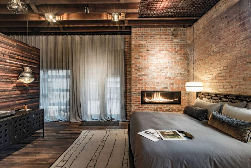 The comfortable gray bed is lit with a warmth from the round pendant light augmented by the fireplace on the side that is inlaid in a red brick wall topped with a ceiling filled with exposed wooden beams matching the hardwood flooring.