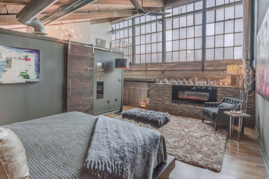 This bedroom looks like its part of a renovated factory that has a wooden shed ceiling with exposed beams, pipes and vents paired with large windows filled with frosted glass and a modern fireplace by the foot of the bed that has a sitting area.