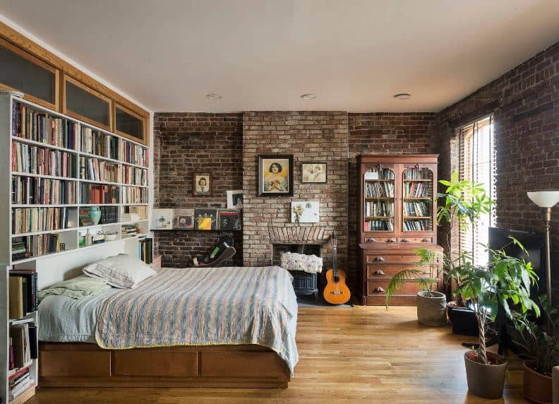 This cozy and homey industrial-style bedroom has a headboard with built-in bookshelves adjacent to a wall of red bricks that houses a fireplace and an antique bookshelf and dresser that matches with the wooden frame of the bed.