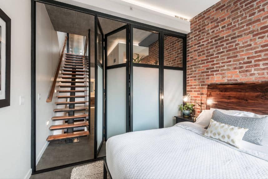 This small industrial style bedroom has a wall of frosted glass that folds to open to the wooden staircase. Adjacent to this is the red brick wall behind the wooden headboard of the bed over a concrete floor with a beige area rug.