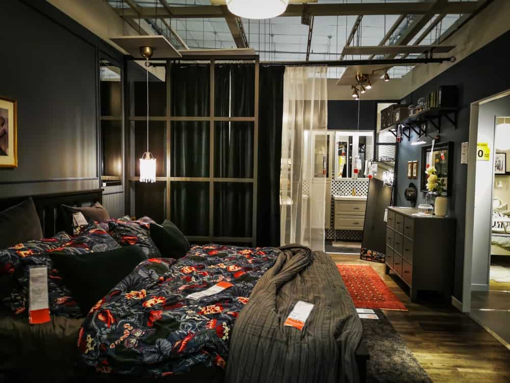 This industrial-style bedroom has hardwood flooring with a gray hue that matches with the sheets of the traditional bed as well as the dresser and shelves. This is darkened by the dark gray walls and illuminated by pendant lights.