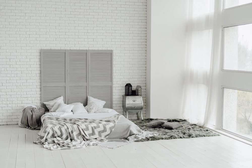 The sheer curtained glass windows bring in an abundance of natural lighting that brightens up the white textured wall with a brick wall pattern. This is complemented by wooden divider that is used as a tall headboard for the platform bed on the light gray flooring.