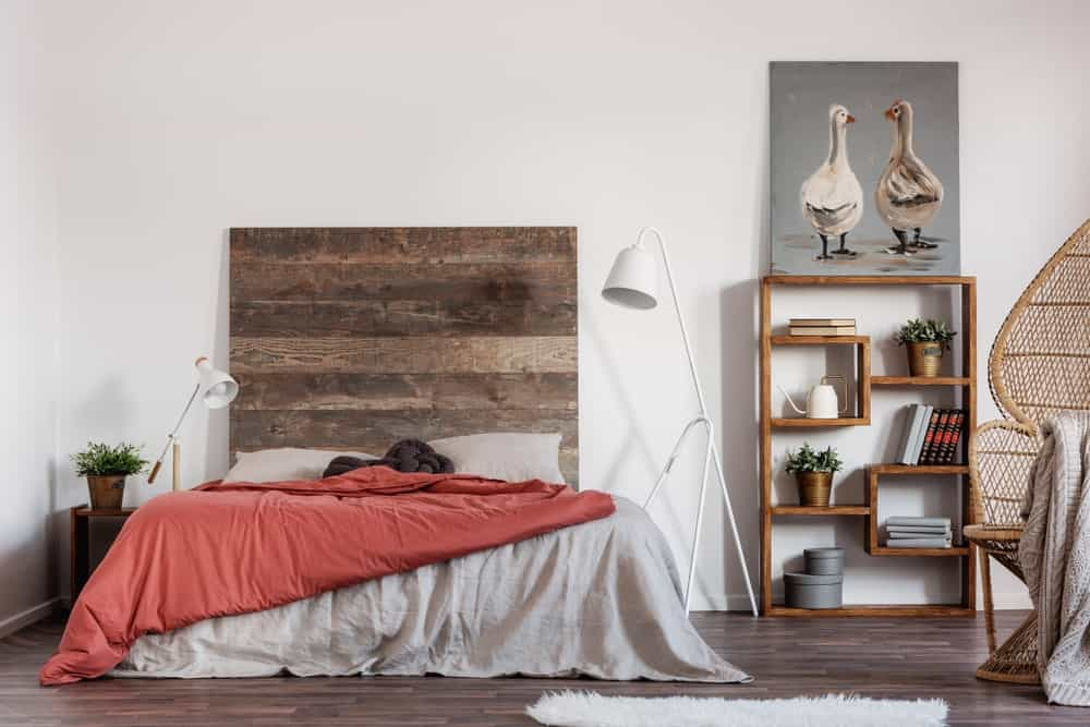 The back-less wooden shelf on the right side of the bed stands out against the white wall. This is also true for the large wooden headboard with a hue that matches that of the hardwood flooring and the bedside table.