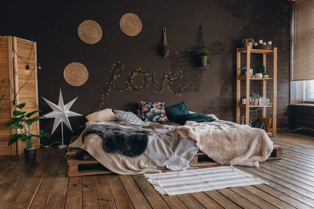 This industrial-style primary bedroom has a romantic vibe to it with a platform bed frame made of pallet crates that blend with the distressed hardwood flooring and complements the wooden structures of the room that stand out against the dark gray wall.