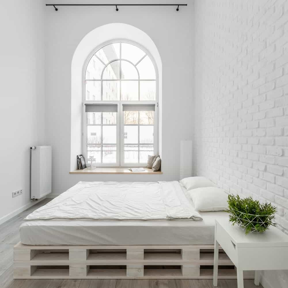 The brightness of this industrial-style bedroom comes from the tall arched window that brings in an abundance of natural lighting that makes the white walls and bed glow. This bed is on a stack of pallets forming a platform for the bed cushion.
