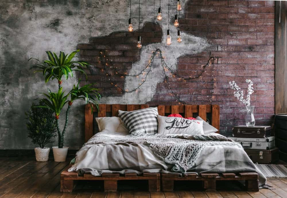 This industrial-style bedroom has a customized platform bed frame made of wooden pallet crates that also make up the wooden headboard with a redwood hue. This complements the red brick wall with a design that fades into a concrete wall.