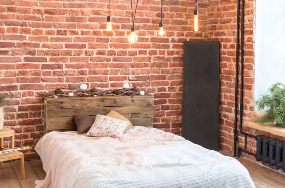 The rustic wooden headboard of the platform-style bed matches the hardwood flooring and its plank finish. This is surrounded by red brick walls that are accented with black pipes of the heater and a variety of pendant lights.