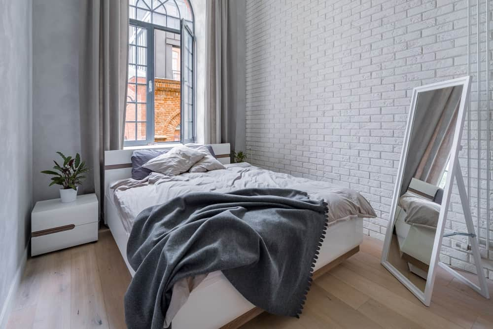 This industrial style bedroom wakes you up with a lovely textured white stone wall that matches with the white bed and its white bedside drawers. They all glow from the natural lights of the tall window augmented by a light hardwood flooring.