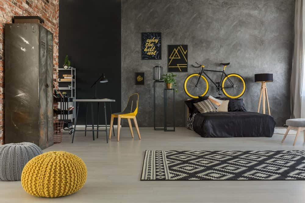 The industrial-style gray concrete wall provides a nice complement to the black sheets of the low bed with a wooden headboard that also serves as the stand for the bicycle. This acts as an accent to the gray wall along with framed artworks and a standing lamp.