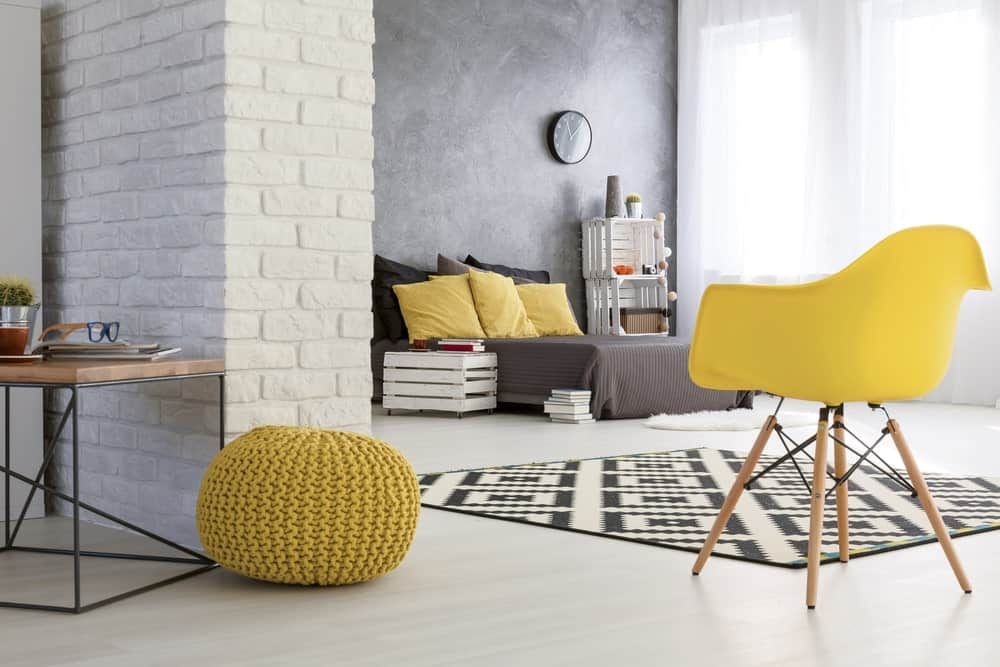 The industrial white flooring is a perfect match for the white stone wall with a brick wall pattern to it. This is brightened by the tall curtained windows that also brighten up the contrasting dark gray bed.