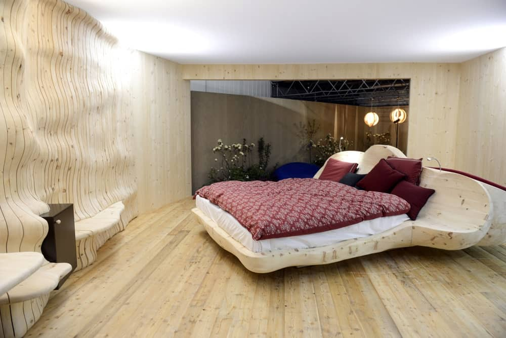 This industrial-style bedroom has light hardwood flooring that blends with the unique customized bed frame that has a fluid shape. This aesthetic is matched by the wall of the same material and hue that seem to flow and ripple to create shelves.