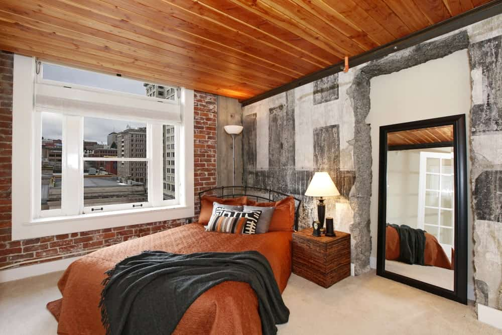 The four surfaces of this industrial-style bedroom has a different hue and material. The flooring is beige, the two adjacent walls flanking the bed is also varied with the left side made of brick and the right made of concrete and finally the ceiling is made of wood.