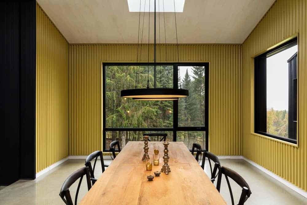 The black wooden dining chairs match with the black circular pendant light that stands out against the yellow industrial-style walls. This is paired with gray concrete floors and large glass windows that brighten up the room.