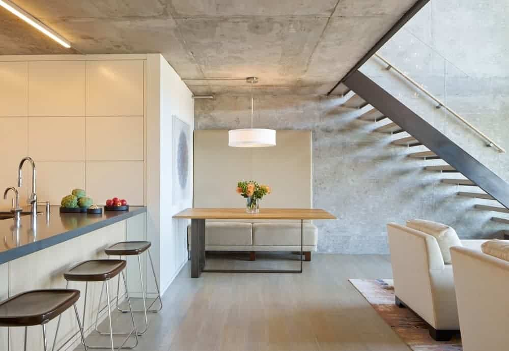 The simple informal dining area is tucked away in a corner by the kitchen and the living room. It has a beige cushioned bench with a large backrest that complements the gray concrete walls and ceiling that supports a white pendant light over the wooden table.