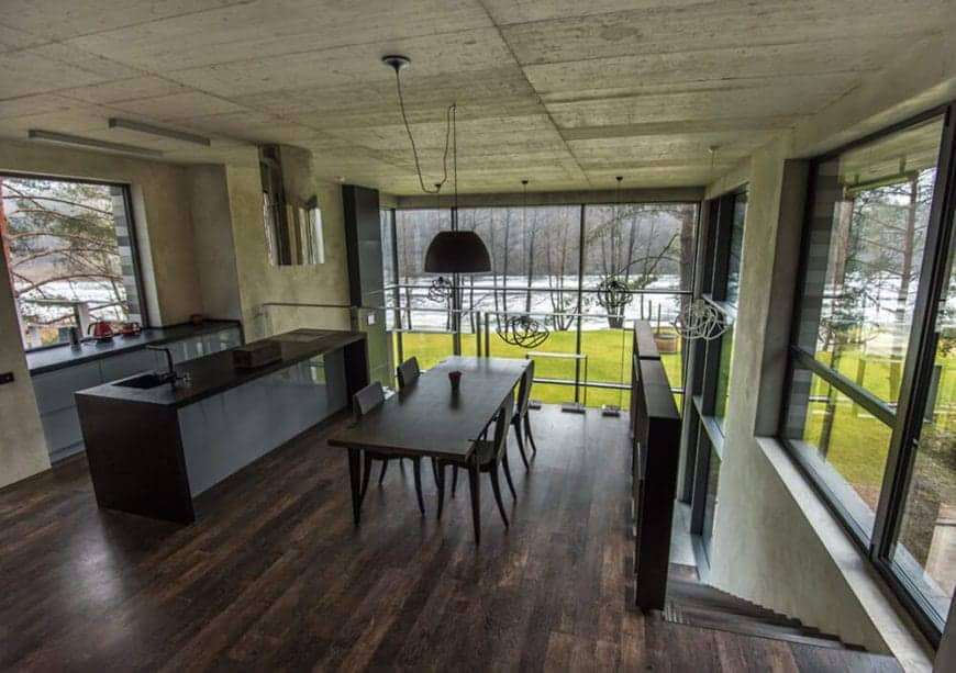 This second floor dining area is beside the kitchen with the same dark hardwood flooring and gray concrete ceiling that supports a large black dome pendant light over the dark wooden table and its dark chairs brightened by the large glass windows.