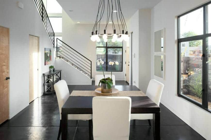 The white cushions of the dining chairs surrounding the black square dining table stands out against the black industrial-style flooring that is illuminated by the tall window and augmented by the industrial-style chandelier.