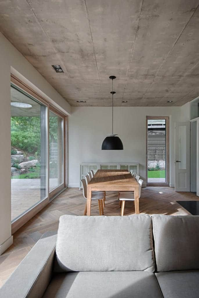The simple wooden dining table stands out against the gray concrete ceiling that hangs a large dome pendant light with a black hue that contrasts the white modern dining chairs over a distressed hardwood flooring by the living room.