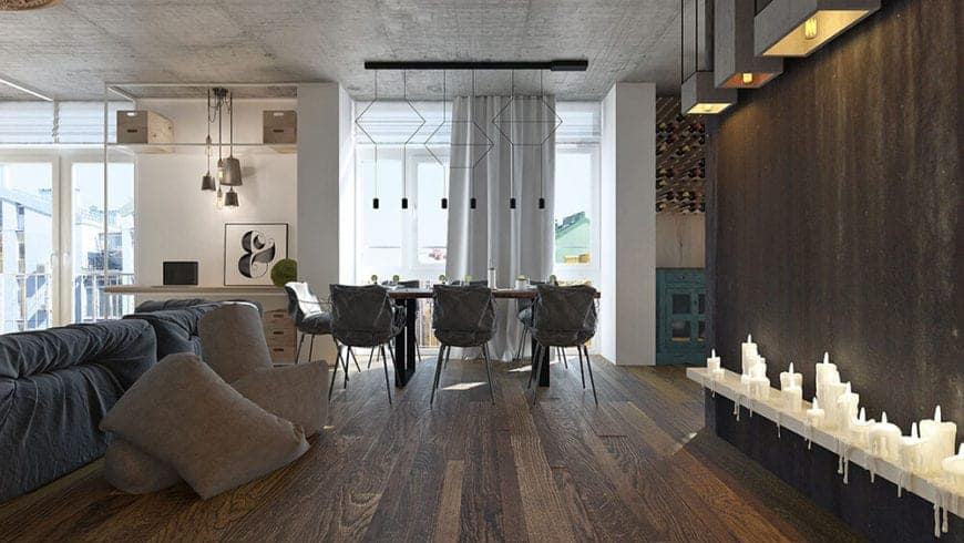 This hallway of dark hardwood flooring and walls with rows of candles leads to a dining area that has the same flooring under a modern row of pendant light that are mounted on the concrete ceiling over the wooden dining table.