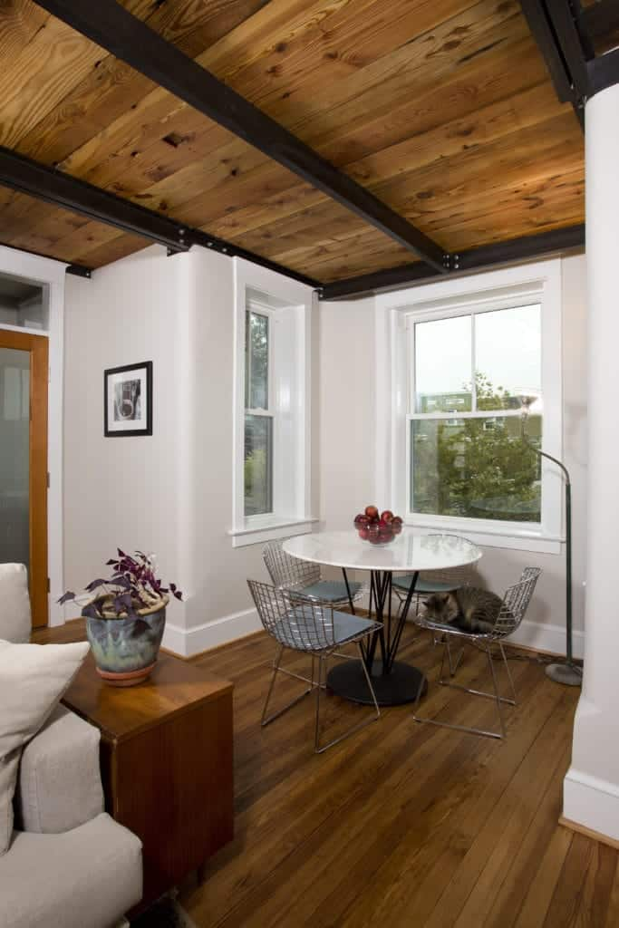 This small industrial-style dining area is in a nook alcove made by white walls with white framed windows and a wooden flooring and ceiling that has exposed metal beams with a contrasting black color matching the legs of the white dining table.