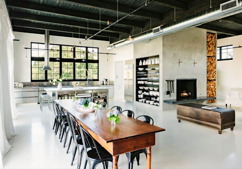 This large and airy dining area by the kitchen and living room has a long wooden rectangular dining table paired with dark metal chairs that stand out against the light hue of the industrial-style flooring paired with a black industrial-style ceiling.